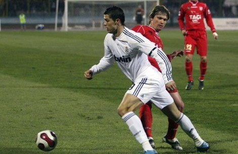 Real Madrid's Cristiano Ronaldo (L) fights for the ball with Endri Vrapi of K.S Gramozi Erseke during their friendly soccer match at Qemal Stafa stadium in Tirana January 20, 2010.  REUTERS/Arben Celi (ALBANIA - Tags: SPORT SOCCER)