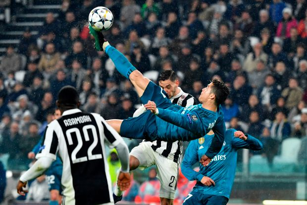 TOPSHOT - Real Madrid's Portuguese forward Cristiano Ronaldo (C) overhead kicks and scores during the UEFA Champions League quarter-final first leg football match between Juventus and Real Madrid at the Allianz Stadium in Turin on April 3, 2018. / AFP PHOTO / Alberto PIZZOLI (Photo credit should read ALBERTO PIZZOLI/AFP/Getty Images)