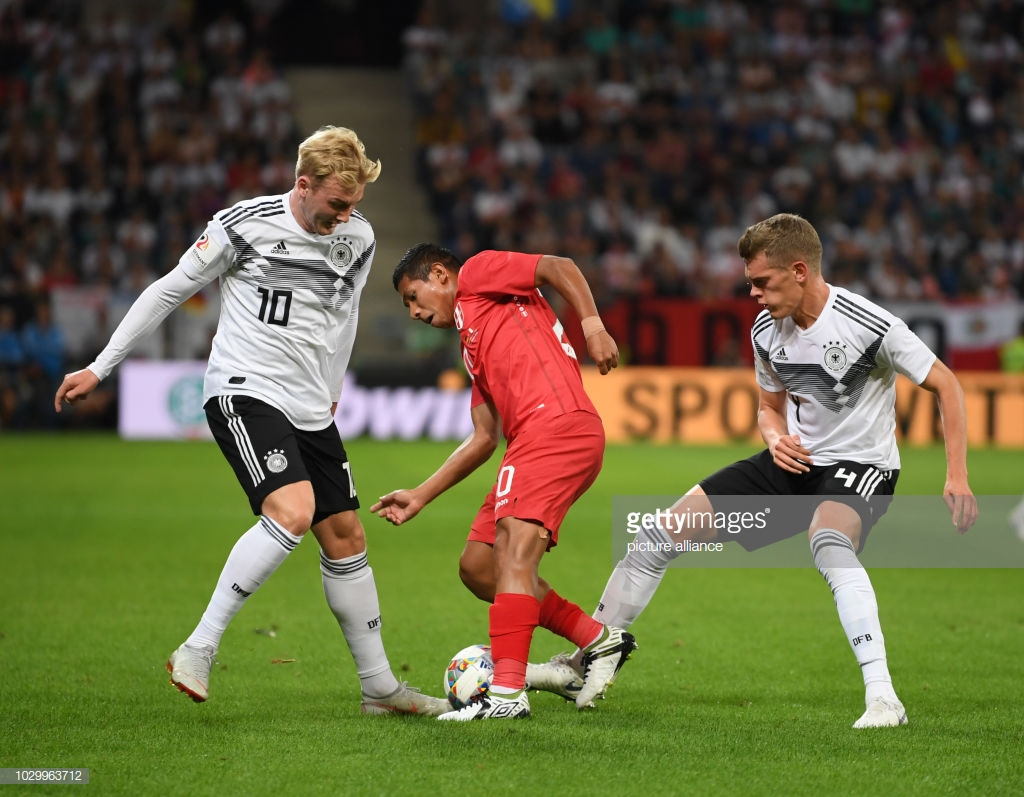 09 September 2018, Germany, Sinsheim: Soccer Friendly match: Germany vs Peru in the Wirsol Rhein-Neckar-Arena: Julian Brandt (L) from Germany and teammate Matthias Ginter (R) take the ball away from Edison Flores from Peru. Photo: Arne Dedert/dpa (Photo by Arne Dedert/picture alliance via Getty Images)