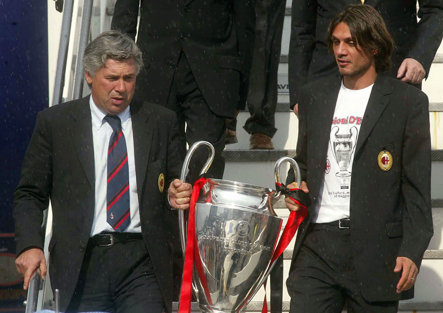 AC Milan coach Carlo Ancelotti (L) descends from the plane together with his captain Paolo Maldini carrying the Champions League Cup, won 28 MAY in the final match against Juventus at the Old Trafford stadium in Manchester, as they arrive at Milan's Malpensa international airport 29 May 2003.  AFP PHOTO /Str  (Photo credit should read STR/AFP/Getty Images)