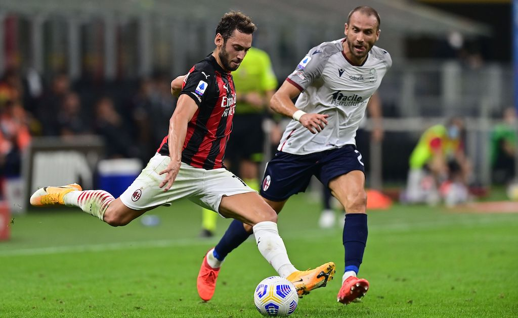 AC Milan's Turkish midfielder Hakan Calhanoglu (L) challenges Bologna's Italian defender Lorenzo De Silvestri during the Italian Serie A football match AC Milan vs Bologne at the San Siro stadium in Milan on September 21, 2020. (Photo by MIGUEL MEDINA / AFP) (Photo by MIGUEL MEDINA/AFP via Getty Images)