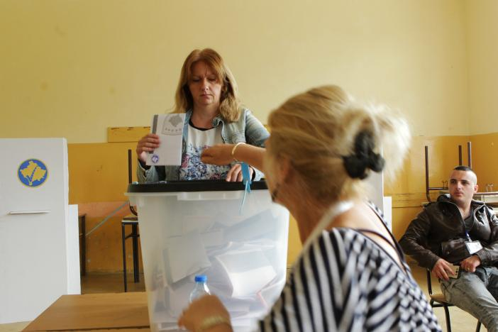 A woman casts her vote at a polling station during the Parliamentary elections in Gracanica