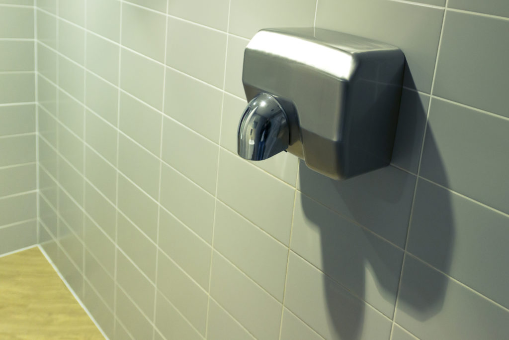Silver hand dryer on grey tiled wall
