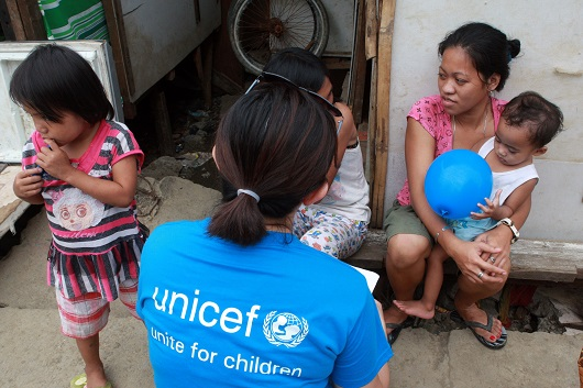UNICEF staff talks to mothers affected by typhoon Haiyan in the village of Rawis Anibong in Tacloban, Leyte.