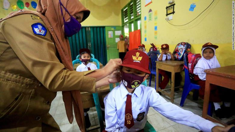 WEST SUMATRA, July 13, 2020  -- A teacher wears face mask for an elementary school student in class on the first day of school in 2020-2021 academic year amid the COVID-19 outbreak in Pesisir Selatan region, West Sumatra, Indonesia, July 13, 2020. Students in Indonesia went back to schools located in low-risk areas under tight health protocols after the closure of education facilities for months due to COVID-19 pandemic. (Photo by Andri Mardiansyah/Xinhua via Getty) (Xinhua/Andri Mardiansyah via Getty Images)